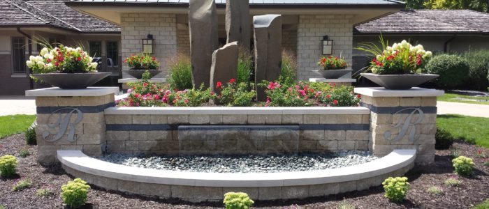 Photo of a waterfall landscape feature made of gray pavers with an arch in the front which holds the water. On top of the pillars on either side are plants, and around the waterfall is landscaping with mulch.