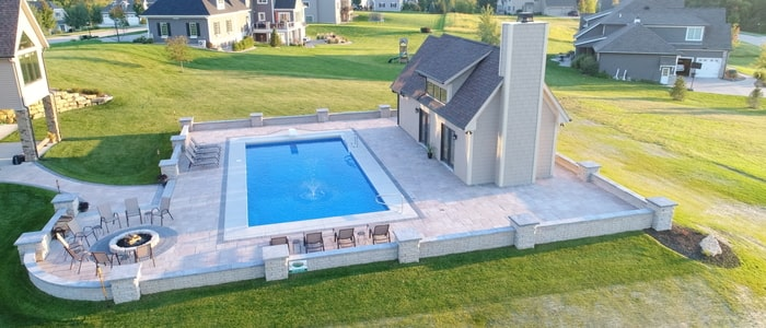 poolscaping with firepit and pool house